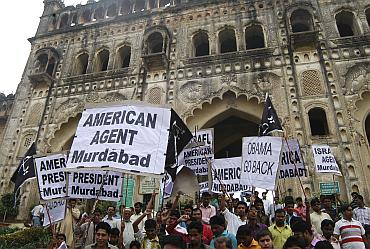 Demonstrators hold placards as they participate in a protest against US President Obama' visit to India, in Lucknow