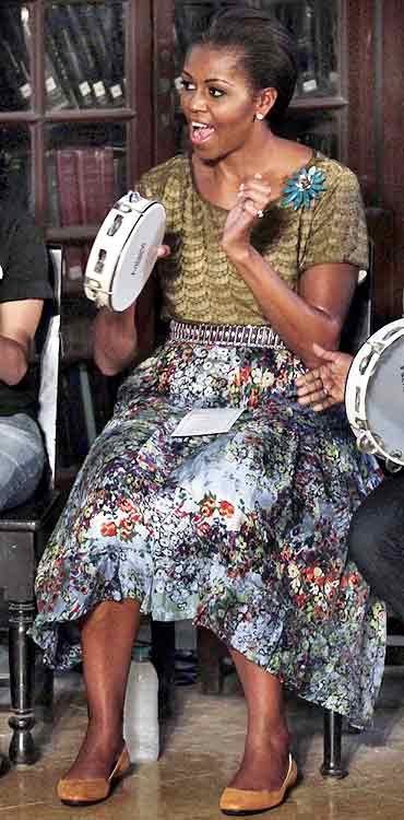 Michelle Obama plays a tambourine for the children