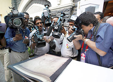 Media crowd round US President Barack Obama's handwritten note at the 26/11 memorial