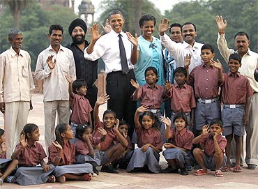 Barack and Michelle Obama with workers who restore historical buildings and their children
