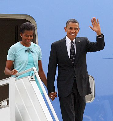 US President Barack Obama waves beside First Lady Michelle Obama from the steps of Air Force One at New Delhi airport