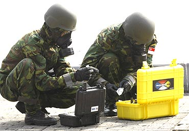 Singapore army personnel in gas masks as part of a drill for the Proliferation Security Initiative Exercise in Japan