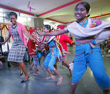 Michelle Obama dances with children during a visit to the Holy Name High School in Mumbai