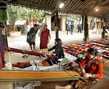 Michelle watches craftswomen working on their handlooms