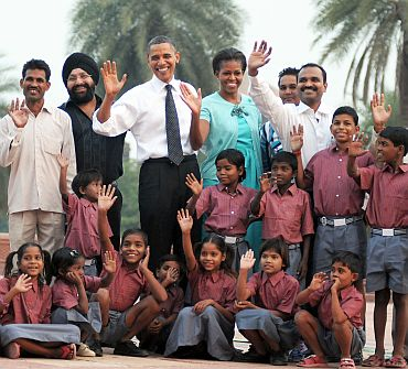US President Barack Obama and the First Lady Michelle Obama pose for a photo with the school children of traditional artisans who carried out renovation works at Humayun Tomb