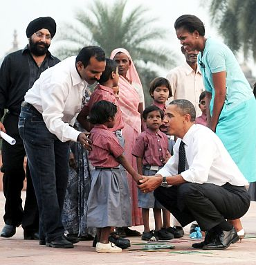 US President Barack Obama and the First Lady Michelle Obama interacting with the school children of traditional artisans who carried out renovation works at Humayun Tomb