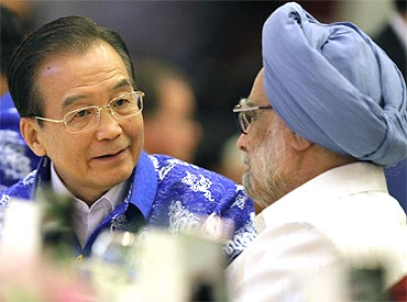 China's Premier Wen Jiabao talks with PM Dr Singh during a gala dinner with other Asian leaders at the 17th ASEAN Summit in Hanoi