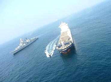 Boat with naval boarding party approaching MV Orinoco with INS Delhi in background