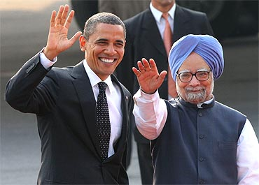US President Obama and Indian PM Dr Singh wave after Obama arrived at New Delhi's airport