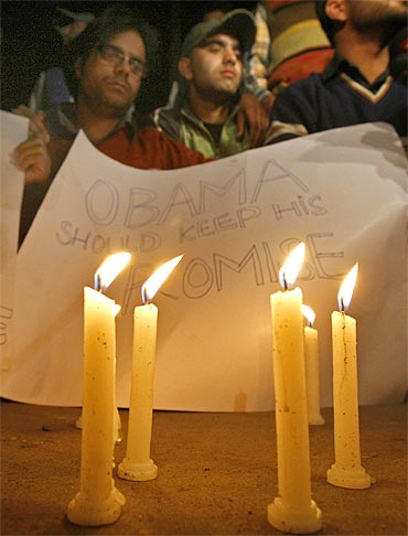 Students of Kashmir University hold a placard behind burning candles to highlight the 'Kashmir issue', during Obama's visit