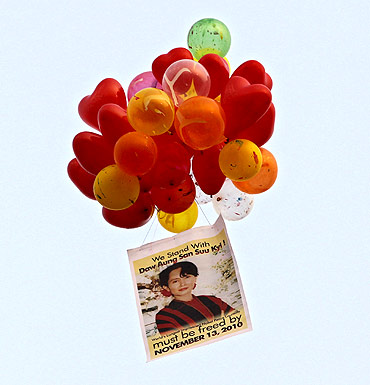 A portrait of Suu Kyi and balloons are released by her supporters during celebrations after her release
