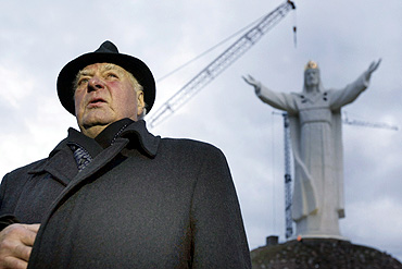 Priest Sylwester Zawadzki poses in front of the giant statue of Jesus Christ