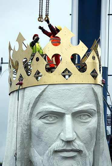 Workers attach chains to the head of the giant statue