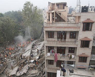 Rescue workers search for survivors under the rubble of a collapsed