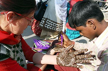 A tatoo artist applies mehendi on a girl's palms in a Srinagar market