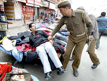 Policemen confront a demonstrator after a protest in Srinagar