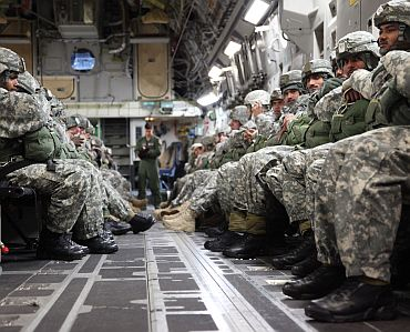 Indian and US army soldiers sit in the back of a C-17 aircraft awaiting commands from jump masters to begin their combined parachute jump November 10