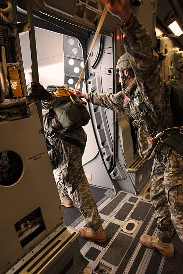 A soldier from 1st Squadron (Airborne), 40th Cavalry Regiment, 4th Brigade Combat Team (Airborne), 25th Infantry Division, assists the jump master inspection of the aircraft door in preparation for the combined parachute jump on November 10