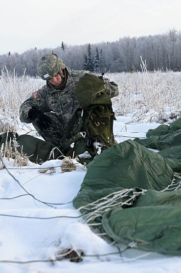 A US soldier packs his parachute after landing at Malamute drop-zone