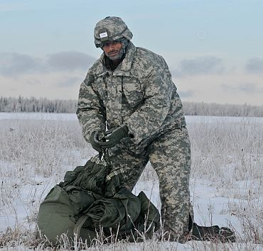An Indian soldier packs up his parachute and looks for the parachute turn-in point at Malamute drop-zone