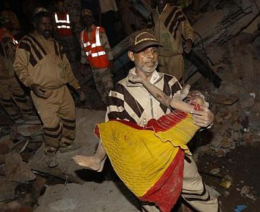 A rescue worker carries an injured girl to safety