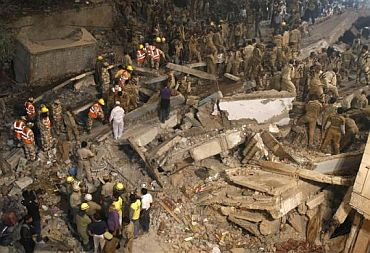 Rescue workers search for survivors under the rubble