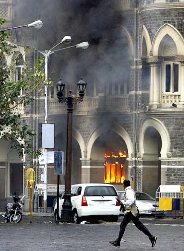 A member of the anti-terrorist squad runs in front of the burning Taj Mahal hotel during a gun battle in Mumbai