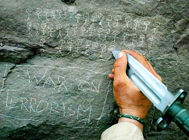 A US Army 10th Mountain Division soldier from Miami, Florida carves the body count that their mortar team has chalked up on a rock, near the villages of Sherkhankheyl, Marzak and Bobelkiel, March 9, 2002