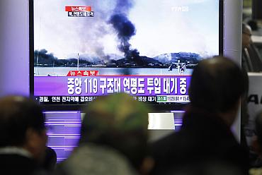 Koreans watch a TV showing smoke rising from Yeonpyeong Island after it was hit by dozens of artillery shells fired by North Korea at  Yeonpyeong Island