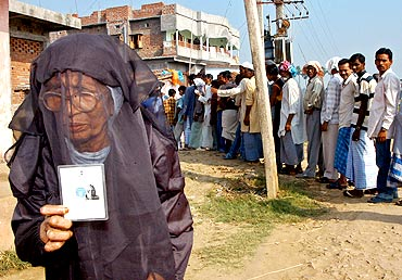 A Muslim woman holds her voter's identity card outside a polling booth in Jahanabad, Bihar