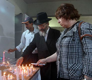 Parents of Rabbi Gavriel light a candle