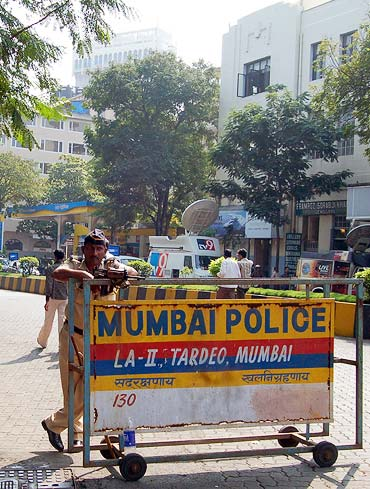 A cop keeping vigil near the state DGP headquarters; The Hotel Taj is in the background