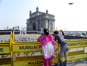 Visitors observe the Gateway of India behind security barricades, adjacent to the Taj Mahal Hotel, at Colaba on Friday