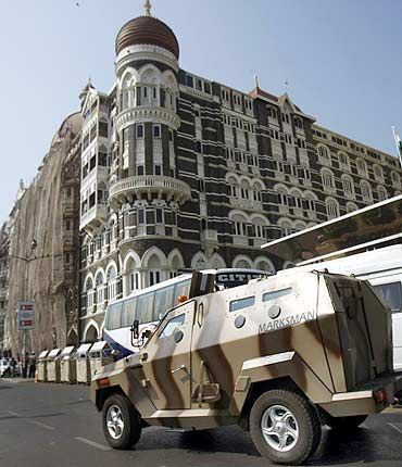 A police armoured car patrols outside the Taj Hotel
