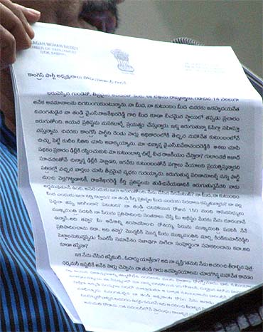 A Jagan loyalist showcases his resignation letter to Sonia Gandhi to mediapersons in Hyderabad