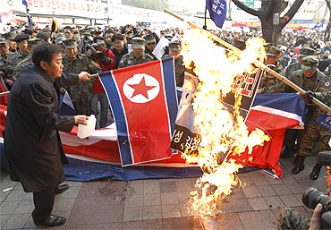 Protesters burn North Korean flags and portraits of North Korean leaders in Seoul