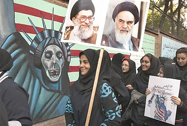 Students take part in a demonstration as one of them holds pictures of Iran's Supreme Leader Ayatollah Ali Khamenei