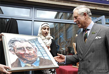 Britain's Prince Charles is presented with a portrait of himself