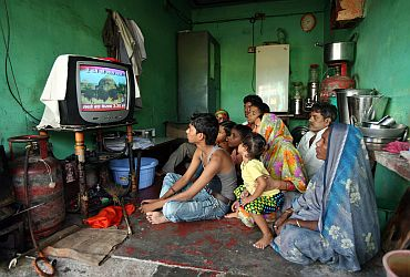 A family watches a TV news channel in a room in Ayodhya on Thursday