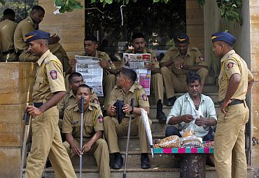 Policemen keep a watch outside a residential colony in Mumbai on Thursday