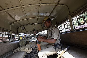 A policeman checks his gun as he sits inside a police vehicle in Lucknow on Thursday