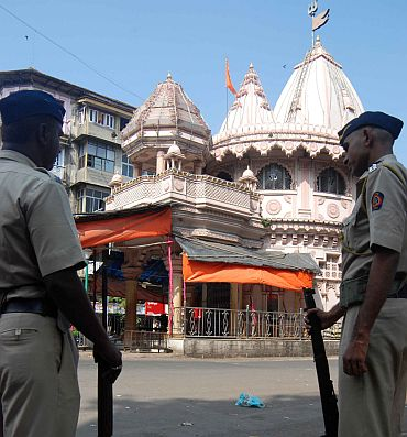 Policemen stand guard in front of a temple in Mumbai on Thursday