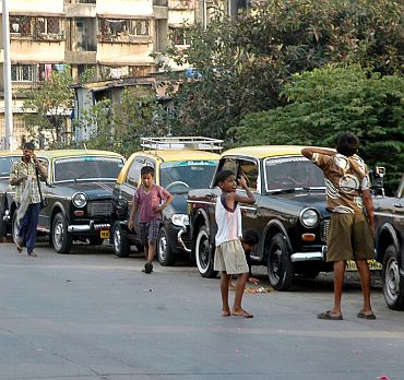 Children play on a deserted street beside a line of stranded taxis in Mumbai on Thursday