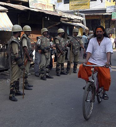 A priest cycles past paramilitary troopers guarding a road in Ayodhya