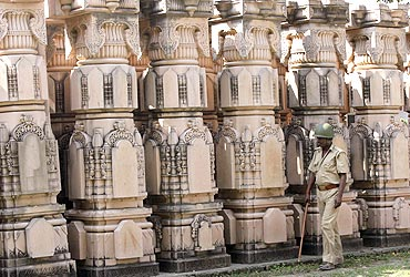 A paramilitary trooper walks past pillars to be used in constructing a temple in Ayodhya
