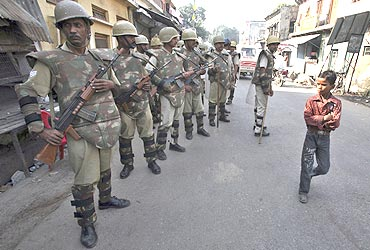 A boy walks past paramilitary troopers in Ayodhya