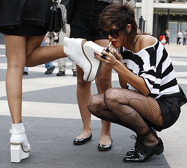 A woman applies lipstick as she arrives at the Lincoln Centre to attend the New York Fashion Week on September 9