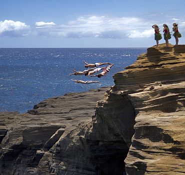 Orlando Duque and Eber Pava of Colombia, Gary Hunt of England, Hassan Mouti of France and Kent De Mond of the US dive from a 16 metre (53 feet) rock at Lana'i Lookout as some local hula girls look on in the lead up to the final round of the 2010 Red Bull Cliff Diving World Series in Oahu, Hawaii, on September 8