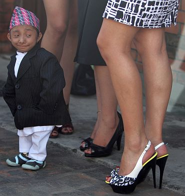 Khagendra Thapa, who is expected to be the world's shortest man in October when he turns 18, looks at the legs of Miss Nepal beauty pageant winners during a news conference in Kathmandu on September 24, 2010. The Nepal Tourism Board has nominated Thapa and Miss Nepal beauty pageant winners as goodwill ambassadors to promote tourism in Nepal. Thapa will carry the message, 'Shortest man in the world from the highest mountain in the world invites you to visit Nepal'