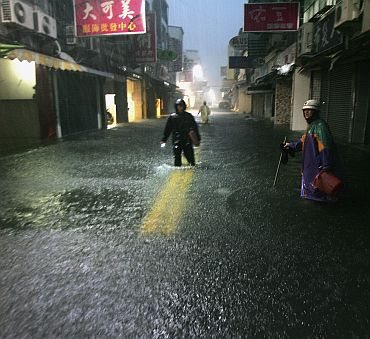 People walk along a flooded street as Typhoon Fanapi hits Kaohsiung City, southern Taiwan on September 19, 2010. Typhoon Fanapi, Taiwan's most severe storm so far in 2010, brought 162 kph (101 mph) maximum wind gusts that caused injuries by toppling scooters, breaking glass and blowing down signs